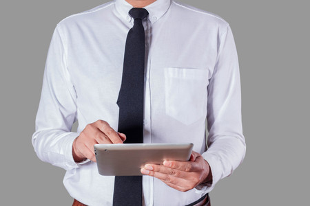 tiedup: Businessmen are using tablets in office.
