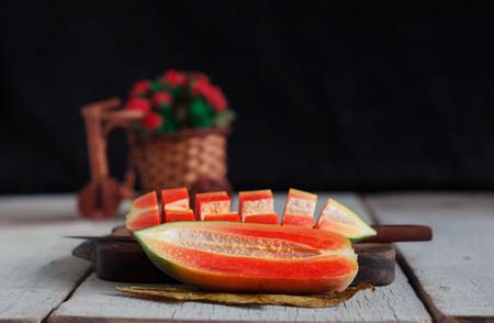 Papaya is half and cut on old wooden floor. Stock Photo