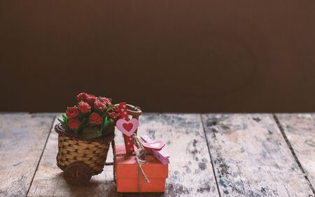 Serce i prezent z kwiatami na stole.