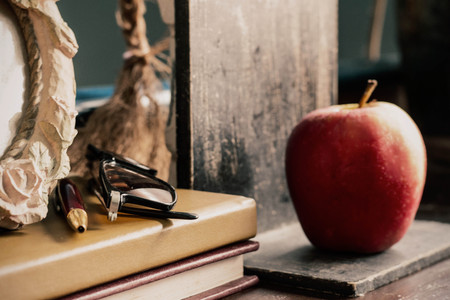 Old stationery and apple on the desk.