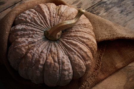 Pumpkin with sack on the old wooden floor.