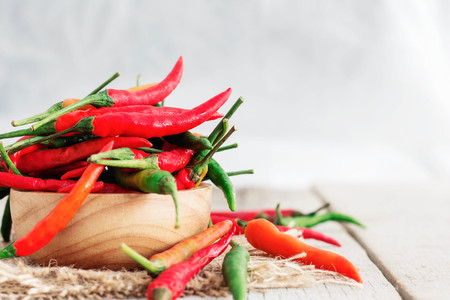 Fresh chilli in a bowl on a wooden table. Imagens - 79143551