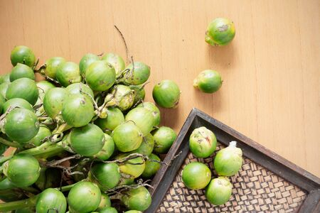 Green betel nut with old wooden tray on the table. Stock Photo