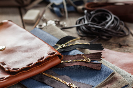 Bags and zip with leather on wooden floor.