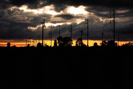 Wind turbines and electric poles with silhouettes at sunset.