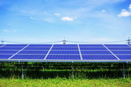 electric grid: Solar panels on grass with blue sky.