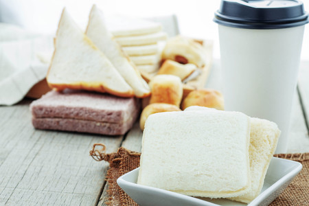 Bread in dish and coffee cup on table. Stock Photo