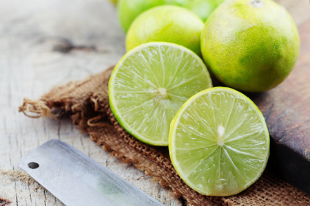 Lime slices and knife on wooden floor.