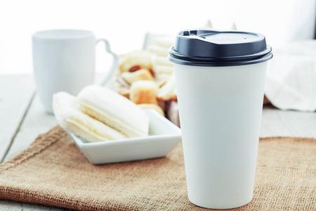 Tazze da caffè di carta e pane sul tavolo.