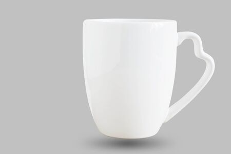 White cup on a gray background. Stock Photo