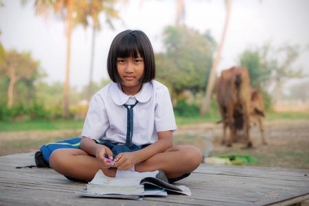Ragazza asiatica del vestito dallo studente che fa i compiti in campagna.