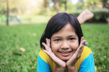 Asiatische Mädchen lächeln glücklich auf dem Rasen.