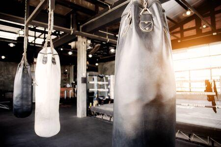 Punching bag hanging in the Thai boxing stadium at sunlight.