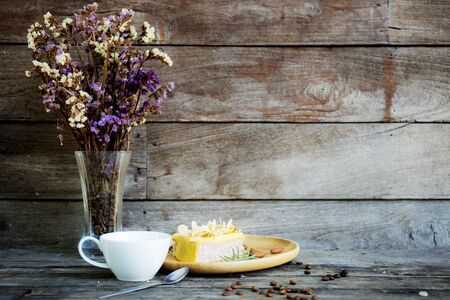 Coffe cup and vase flower on wooden table at wall.
