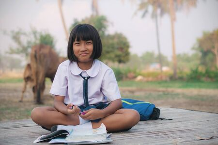 Thai girl sitting on a bamboo mat in the countryside.
