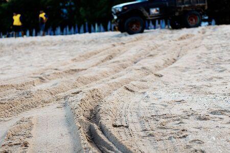 Wheel marks on sand beach at the sea with car background. Reklamní fotografie