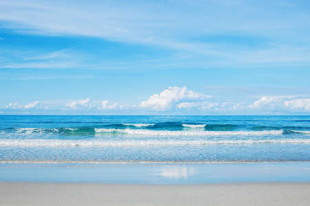 Sand beach and blue waves at the sky in summer.