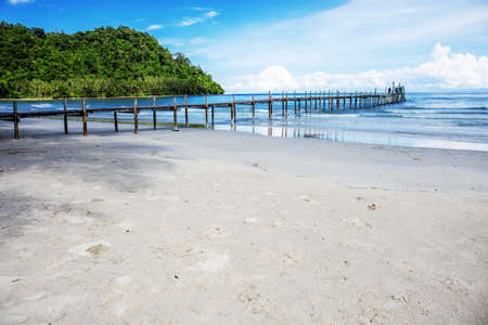 Wooden bridge on beach at sea with the blue sky.