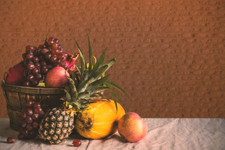 Many fruit basket on the table at a wall.