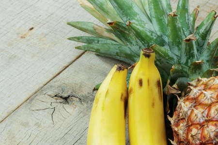 Banana ripe and pineapple on the old wooden.