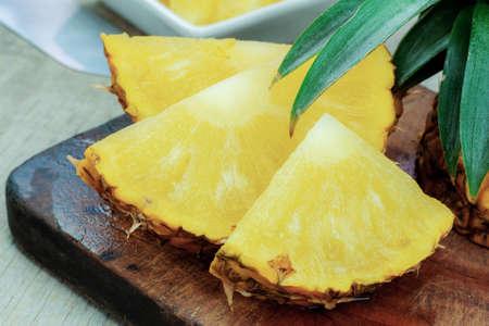 Pineapple ripe of slices on wooden floor.