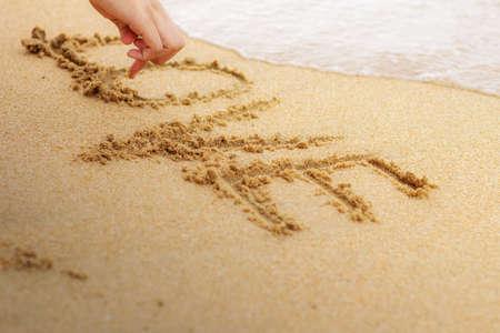 Hand drawing love on sand beach at the sea. Standard-Bild