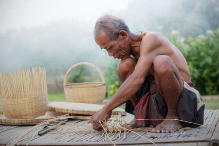 Old people are weaving basket in the countryside.