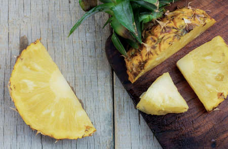 Pineapple slices on the old wooden of table.