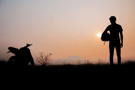 Men of biker in field with the sunset at sky.