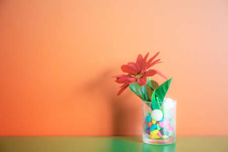 Flowers in a glass of water on wooden at wall.