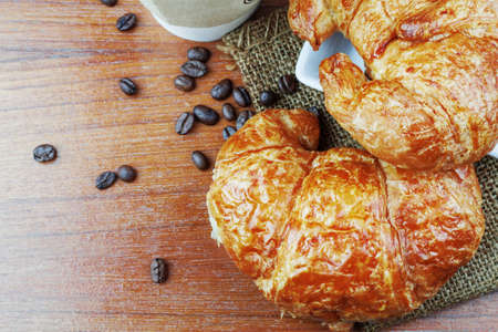 Croissant on plates and coffee on wooden floor.