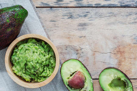 Avocado in a bowl and wooden floor. Standard-Bild