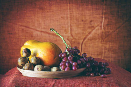Grapes and other fruits on wooden tray.
