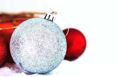 Silver ball with gifts on a white snow.