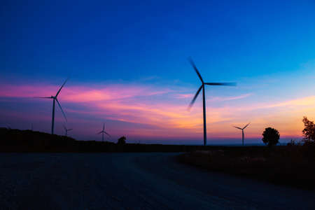 Wind turbine of silhouette with the blue sky in the evening.