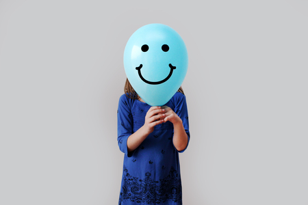 baby girls smiley face: Girl with smiley balloon instead of her face