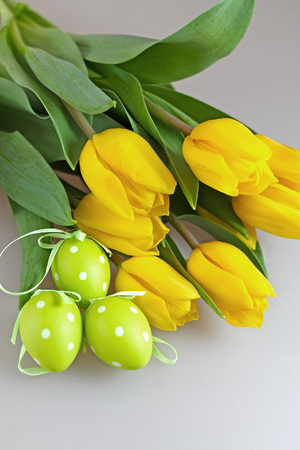 Colored easter eggs and yellow tulips