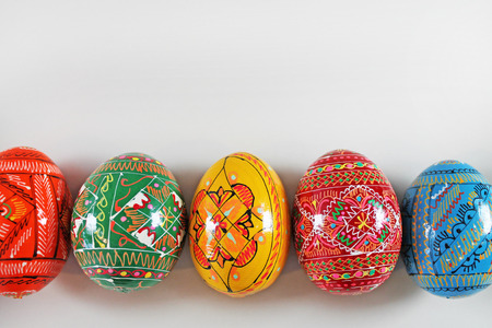 Colorful easter eggs in row on white background. Traditional Czech easter decoration. Stock Photo