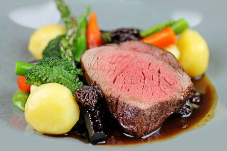 Beef steak with steamed vegetables at restaurant close up.