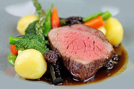 Biefstuk met gestoomde groenten in restaurant close-up. Stockfoto