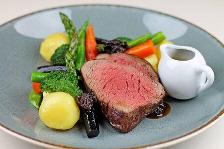Beef steak with steamed vegetables at restaurant close up. 免版税图像