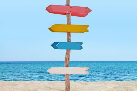 Signboard with arrows on the beach.
