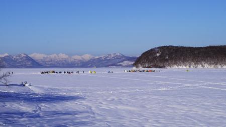 Berry Bay, Vilyuchinsk city, Kamchatka Peninsula, Russia. Group of fishermen on winter fishing.