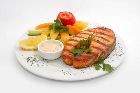 Esturi�n pescado asado servido con vegetales frescos: amarillo pimiento, pepino gr an tomate y perejil  Foto de archivo