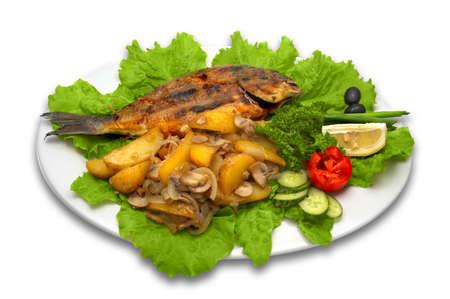 Griled dorada pescado entero, con papa al horno, champi�ones y verduras frescas, establece en hojas de lechuga con la rodaja de lim�n.  Foto de archivo