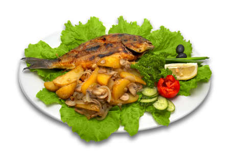 dorada: whole griled dorada fish, with baked potato, mushrooms and fresh vegetables, lays on lettuce leaves with lemon slice.