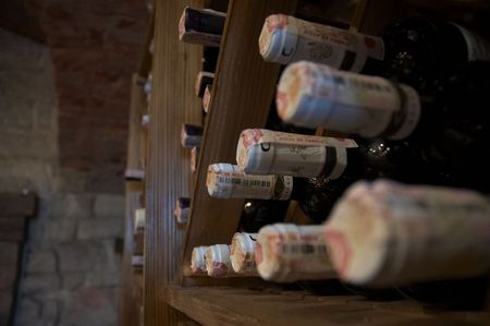 kept: wine bottles laying in wooden rack