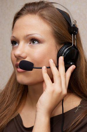 Muchacha bonita de la ayuda de cliente con el receptor de cabeza, escuchando el cliente Foto de archivo