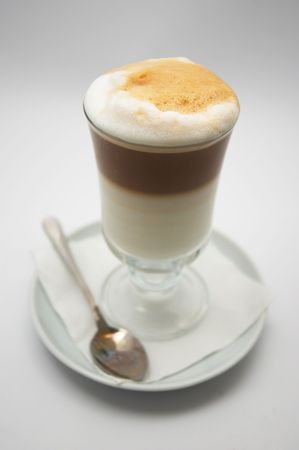 dof: glass mug of just brewed coffee frappe with crisp foam. very shallow dof.
