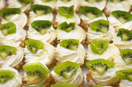 petit: Small cakes (petit four) with custard and kiwi on top. Shallow DOF. Sharp focus on second line.